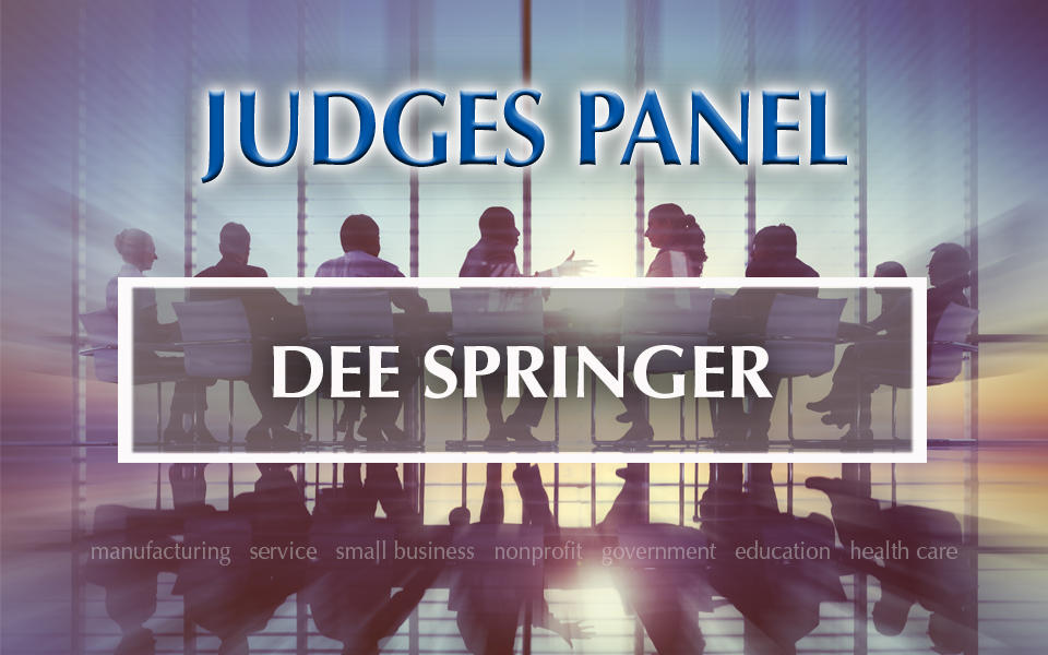 Judges Panel Dee Springer with photo in background of people meeting at a table.