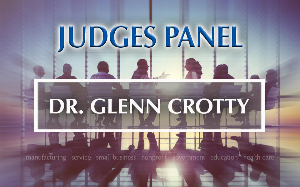 Judges Panel Dr. Glenn Crotty with photo in background of people meeting at a table.