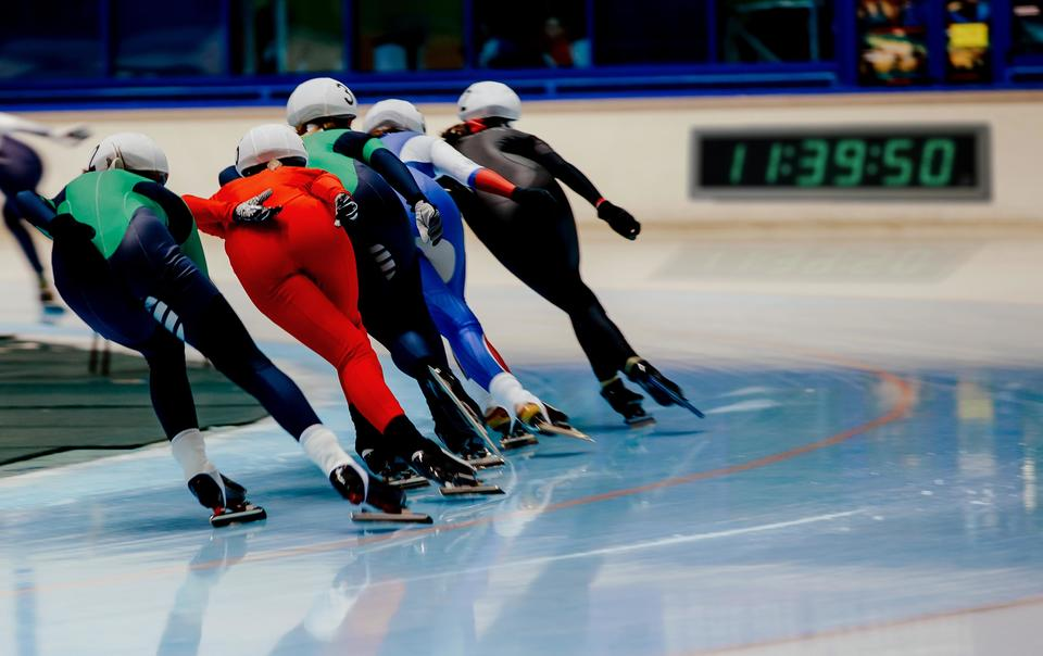"Five speed skaters making a turn on the track. A clock reading ""11:39:50"" is visible on the wall in front of them."