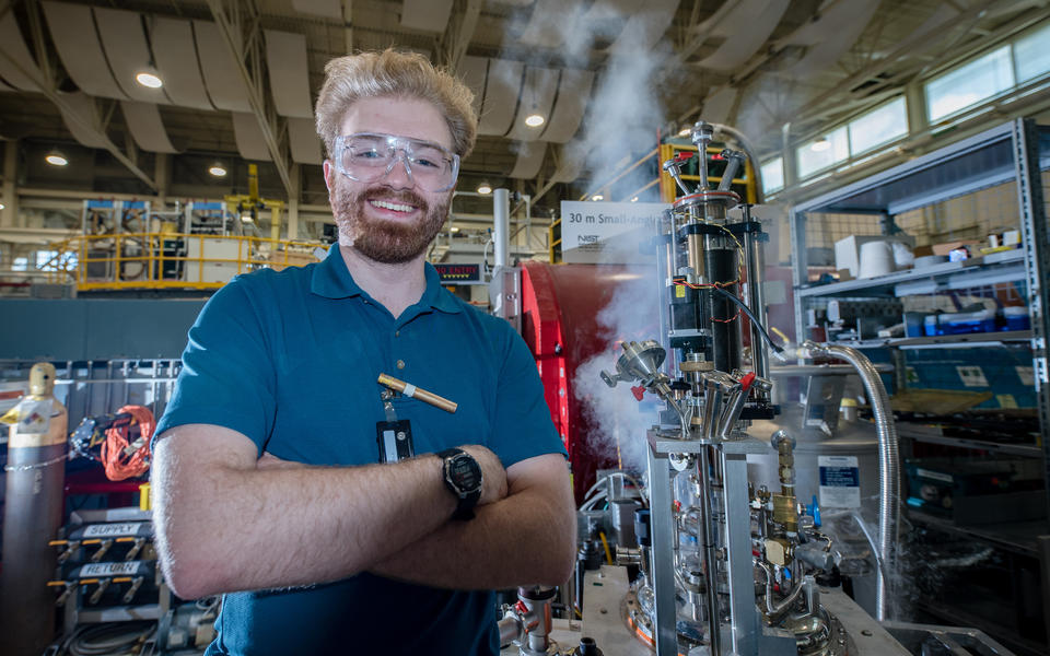 Young man with wild blonde hair and reddish beard smiling beside an AC susceptometer that he helped build