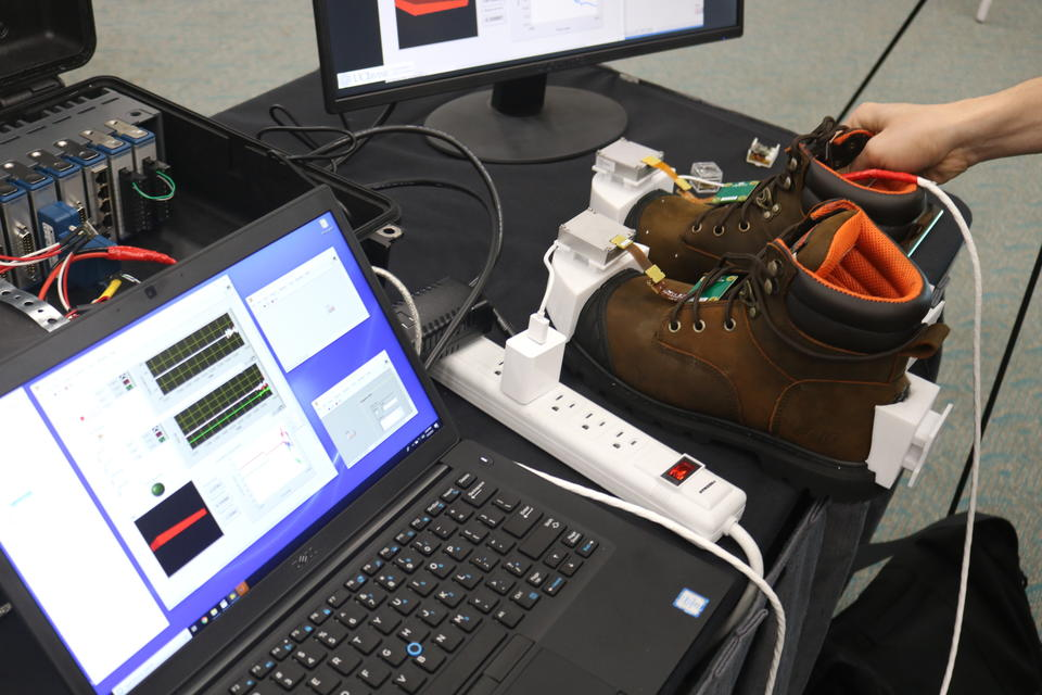 A pair of work boots with location tracking technology built in sitting next to a computer monitor