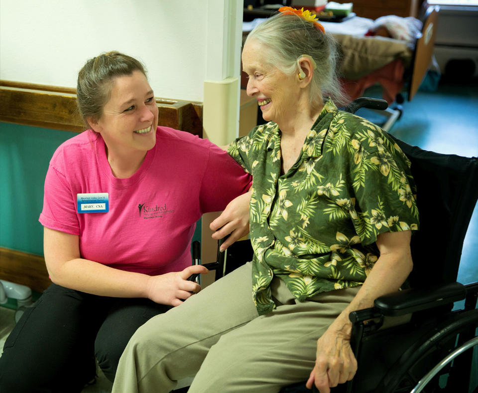 Photo of Kindred Nursing and Rehabilitation Center – Mountain Valley employee helping a patient in a wheelchair.