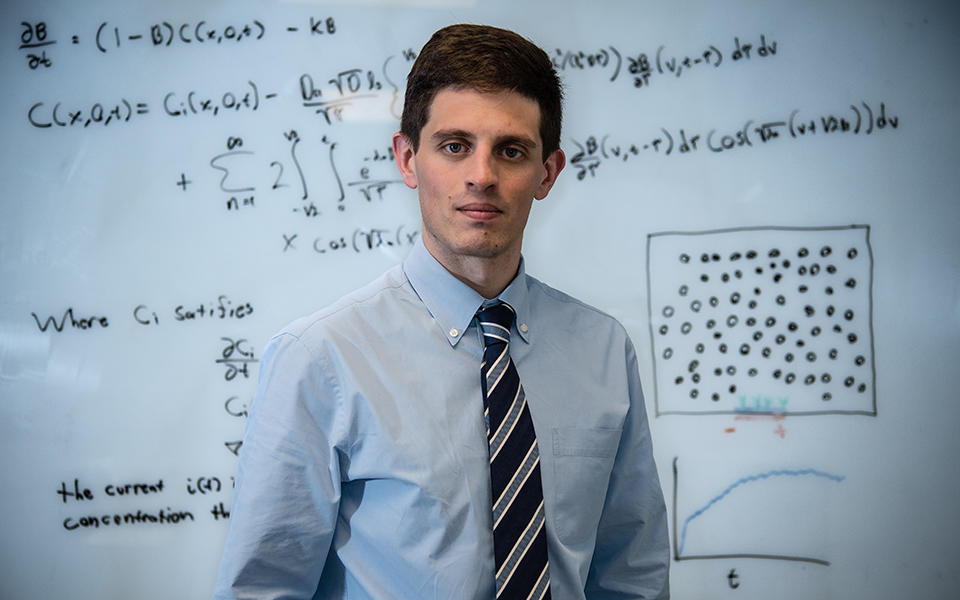 Mathematician Ryan Evans in front of a whiteboard covered in mathematical equations