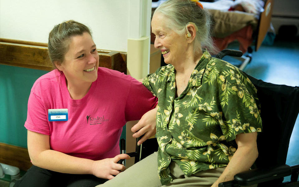 Photo of Kindred Nursing and Rehabilitation Center – Mountain Valley of Cascadia employee helping a patient in a wheelchair.