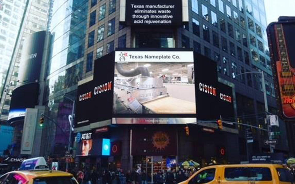 """Texas Nameplate Company billboard in New York City. The caption reads """"Texas manufacturer eliminates waste through innovative acid rejuvenation."""""""