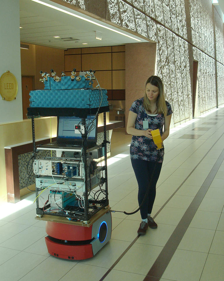Woman in large indoor hallway standing next to tall stack of electronic equipment.
