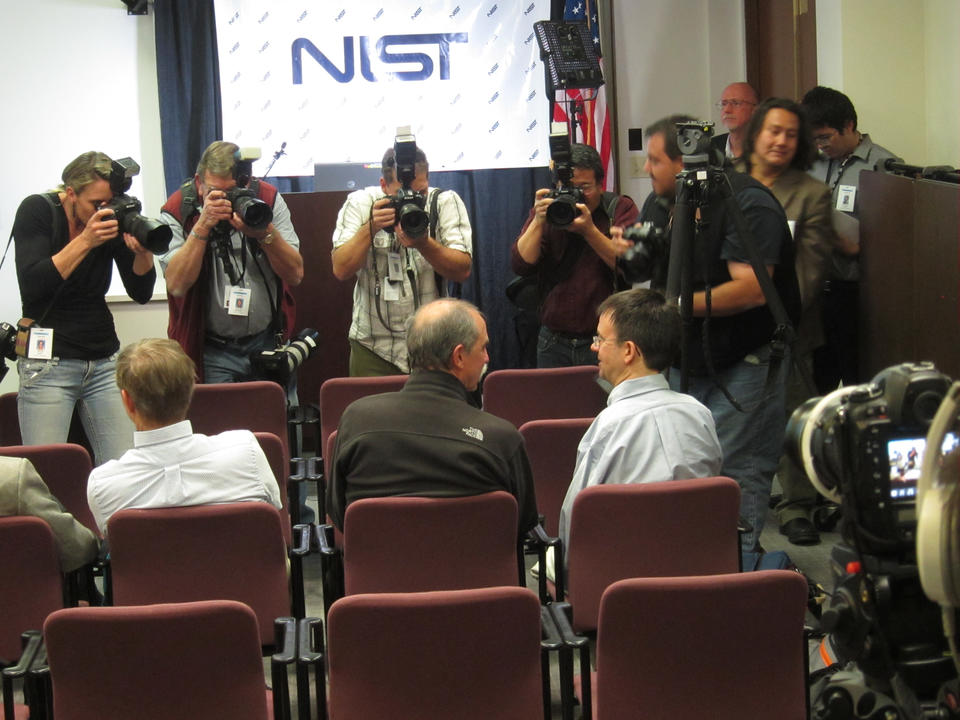 Dave Wineland (left) and Eric Cornell (right) sitting in chairs while photographers take their picture