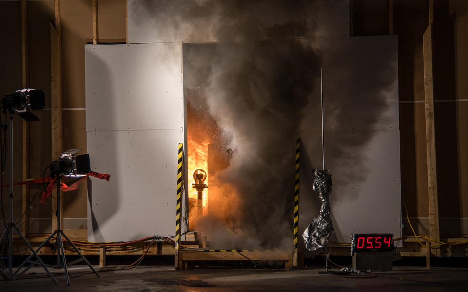smoke billows from the open doorway of a burning test storage room