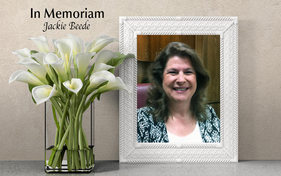 In Memoriam: Photo of Jackie Beede with white lilies in a vase beside frame.