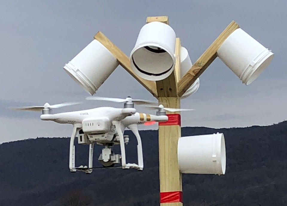 A drone in flight approaches a bucket-shaped target attached to a pole during an evaluation on the NIST performance test course.