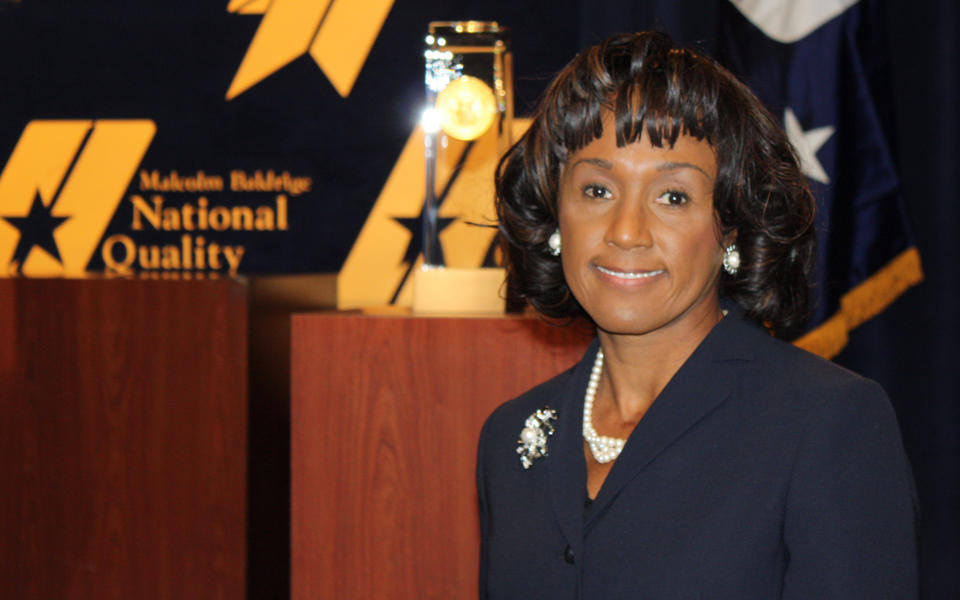 Photo of Jacqueline Calhoun at the Baldrige Award Ceremony with the Award crystal.