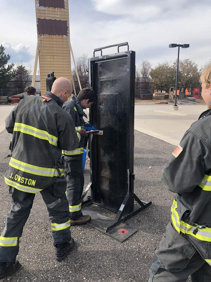 NIST firefighter trainees wait in line to try their hand at breaking down a door at the training facility