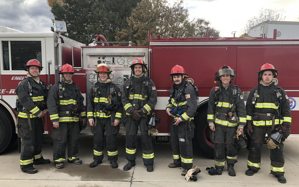 PSCR firefighters for a day post for a photo in full gear in front of a fire truck