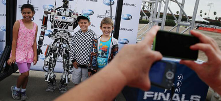 kids posing with a robot for a manufacturing video