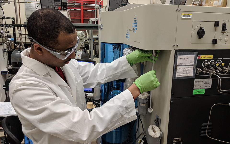 man in a white lab coat and safety goggles loads a metal oxide framework material into a testing machine