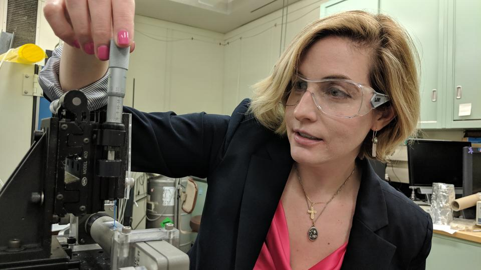 Mary Kombolias load a small blue piece of paper into a dielectric spectrometer.