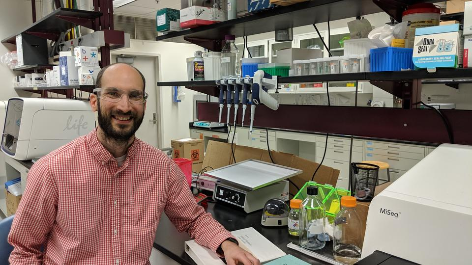 Justin Zook in a lab surrounded by genetic sequencing machines