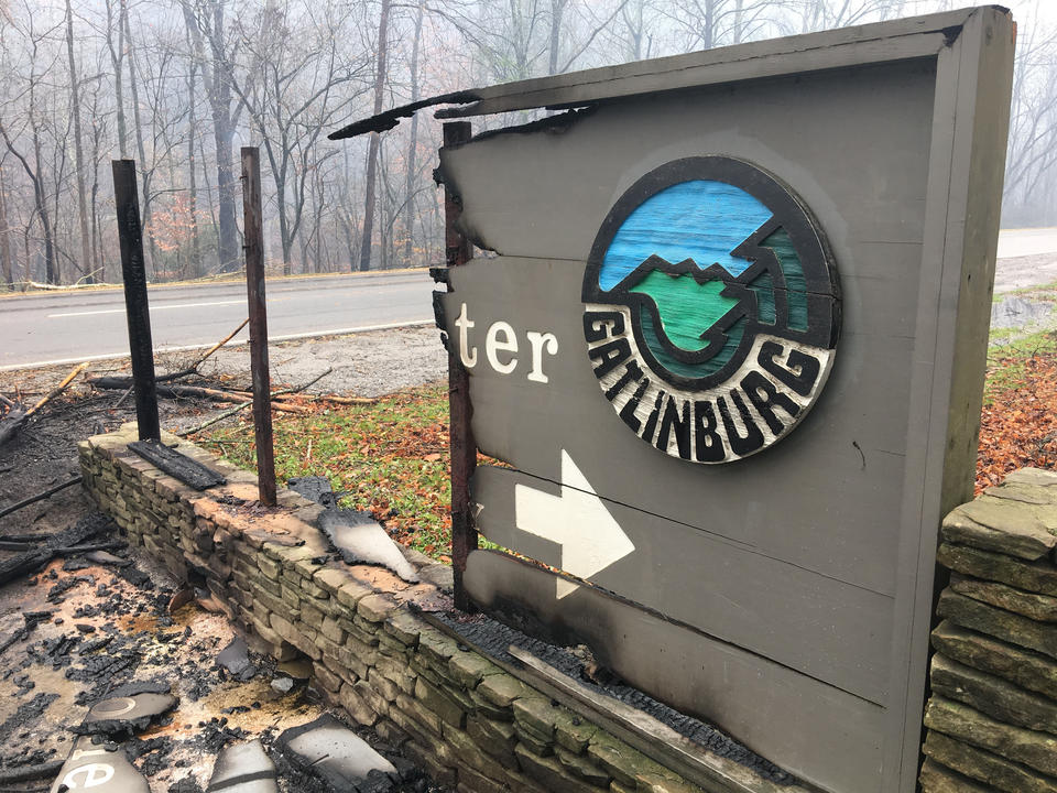 The Great Smoky Mountains National Park Gatlinburg Welcome Center sign is half-burned, leaving only the Gatlinburg name and a white arrow. Debris lies on the ground in front of the sign.