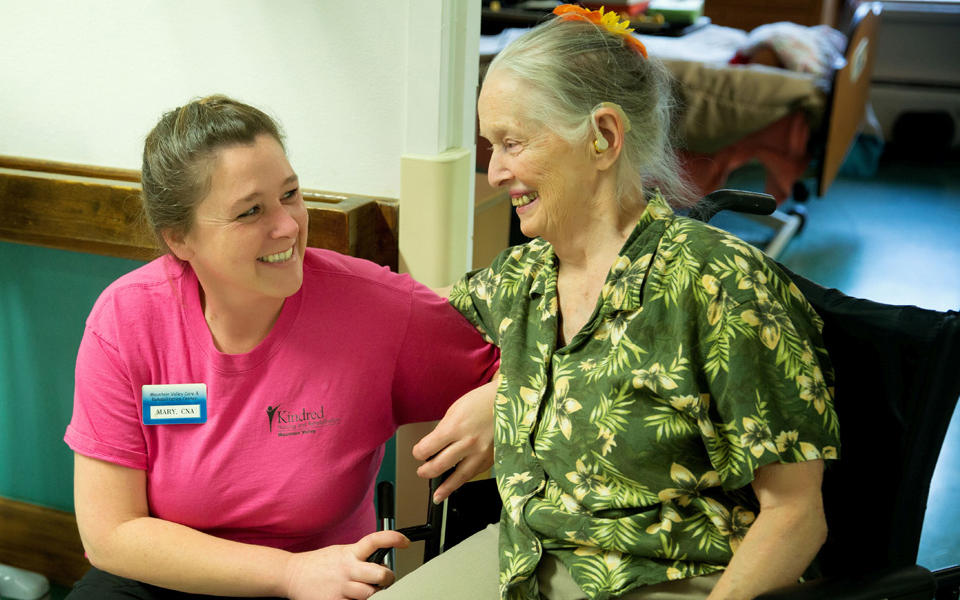 Kindred Nursing and Rehabilitation – Mountain Valley (now Mountain Valley of Cascadia) QE Speaker blog photo of an employee helping an elderly woman.