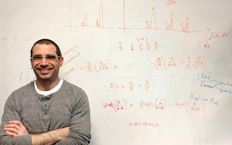 Adam Pintar standing with arms crossed in front of a whiteboard covered with equations and graphs