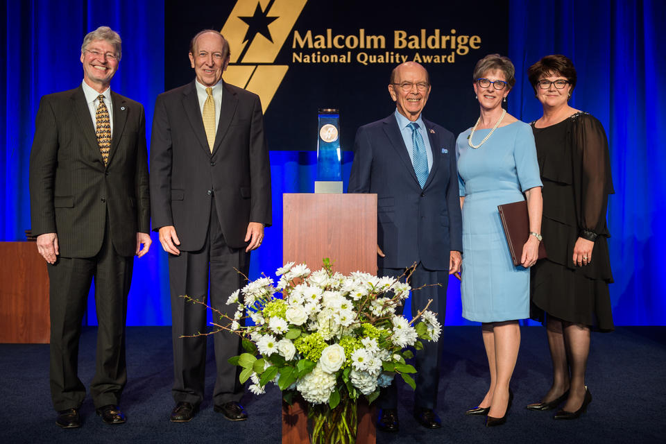 Center: Baldrige Award on a podium. Left: two men in suits. Right: a man in a suit and two women in dresses