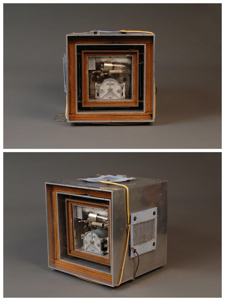 Tow large metal boxes with a wood box in between, then space, then two more metal boxes with wood box inbetween and inside of that is the inside of a quartz time standard