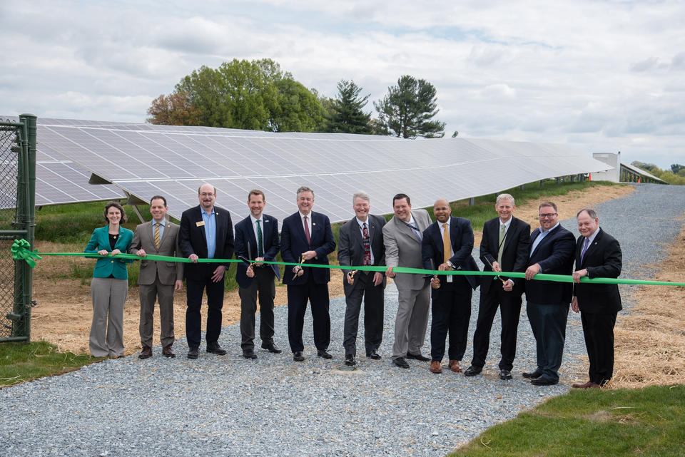Eleven people stand in front of the NIST solar array getting ready to cut an orange ribbon with large scissors.