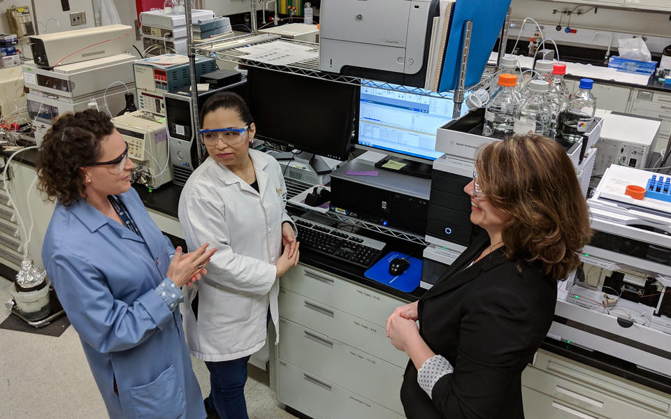 Carolyn Burdette, Laura Regalado and Katrice Lippa having an animated discussion in the lab. Behind them is a computer screen and other laboratory equipment, including a liquid chromatography mass spectrometer.