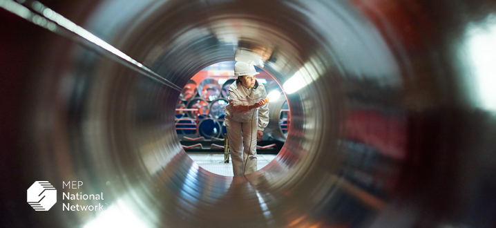 person quality inspecting a large metal pipe