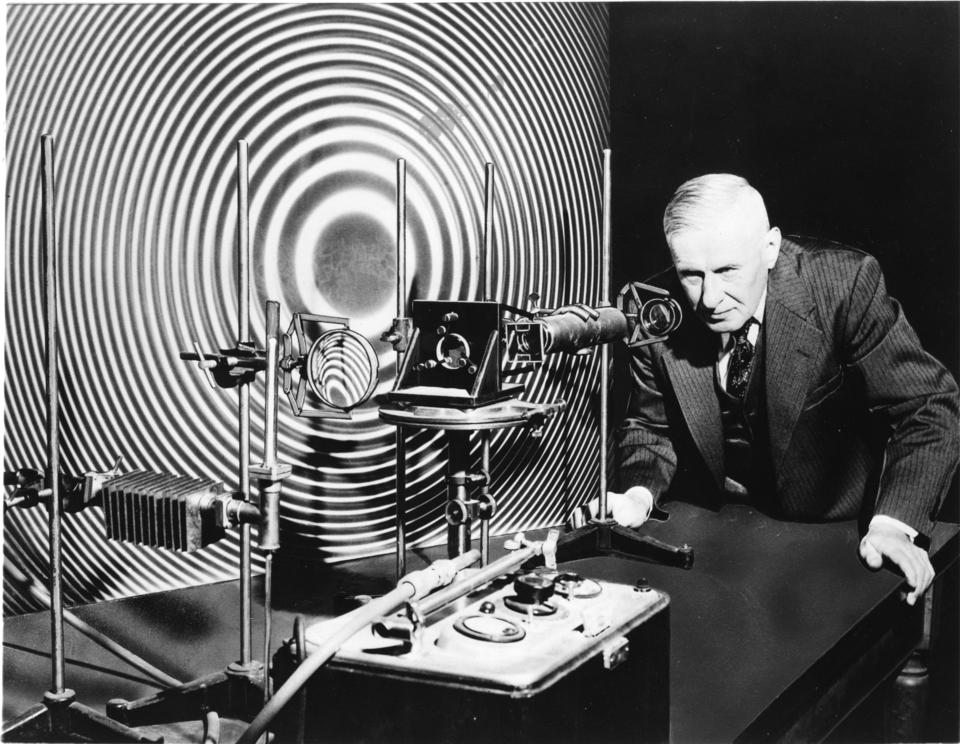 Man stands looking into the eyepiece of scientific equipment. Pattern behind is black and white concentric rings.