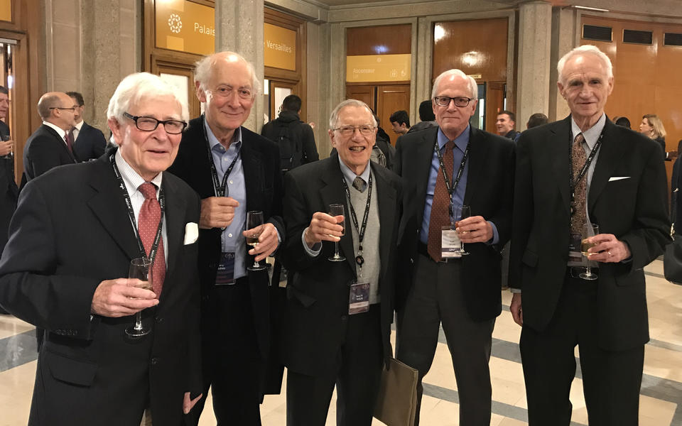 group of five men holding champagne flutes