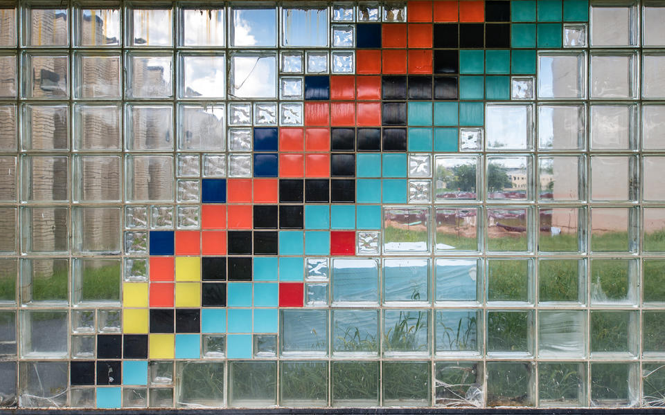 a glass brick wall with blue, orange, yell, black, turquoise, and red bricks in a pattern representing different isotopes