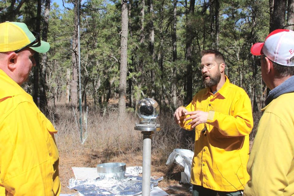 NIST engineer in yellow jacket stands to right of BOB glass globe. To his right and left are two men.