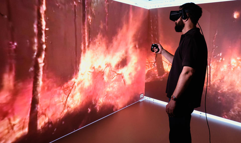 A profile of a man wearing VR equipment is seen against two large screens displaying the view from within a forest fire.