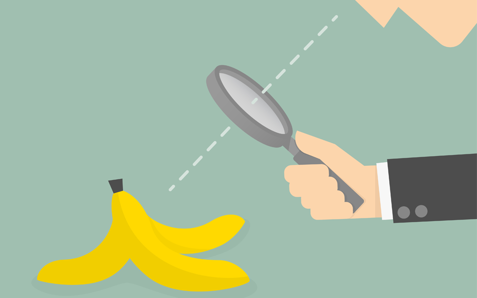 Image of a businessman looking a through a magnifying glass at a banana peel.