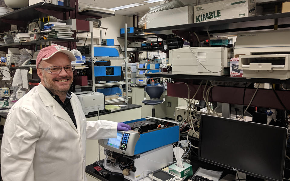 smiling man with a red baseball cap and white lab coat on in a laboratory full of instruments