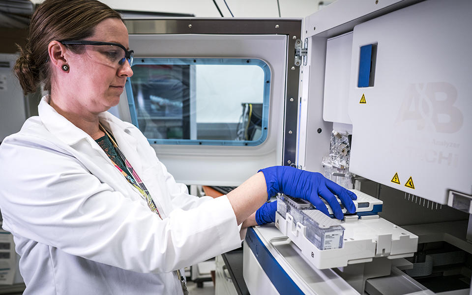 woman loads small plastic vials containing human DNA into a large machine