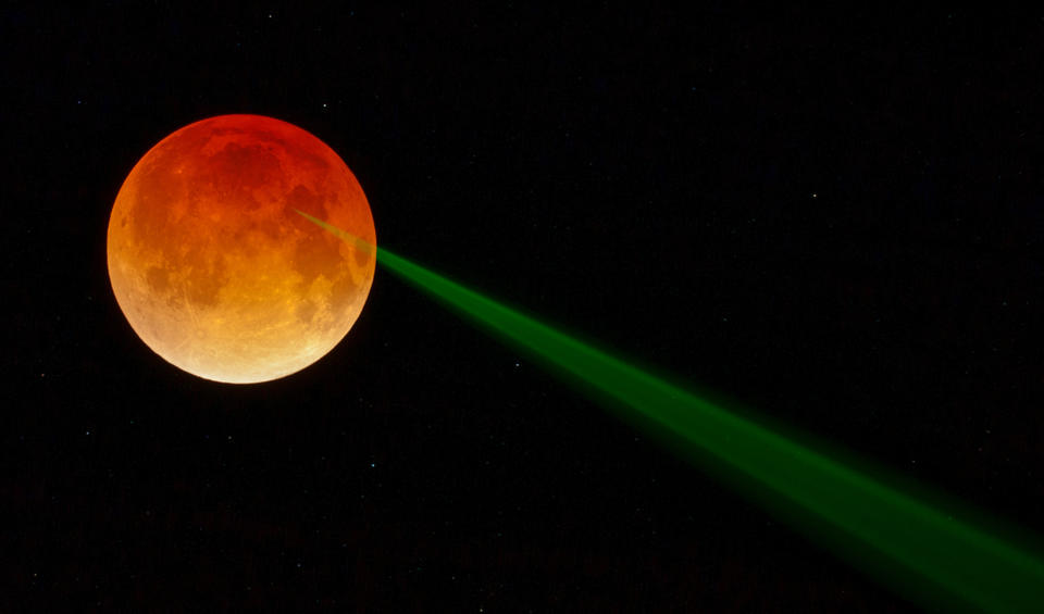 Orange moon with a laser beam being shot at it