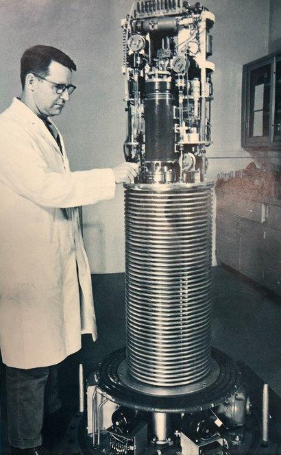 A man in a lab coat stands to the left of a tall piece of equipment