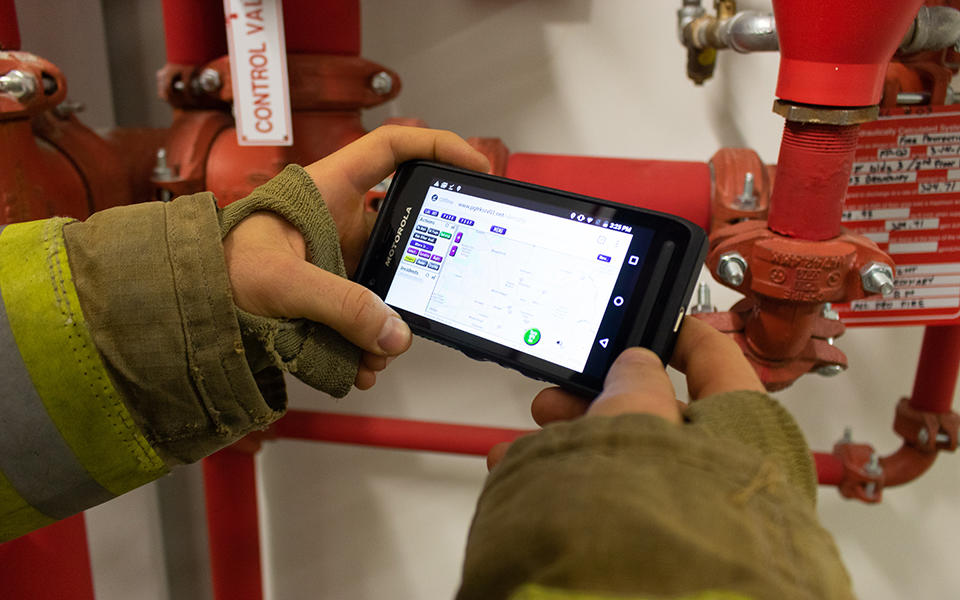 firefighter holding a phone with an app pulled up on the screen