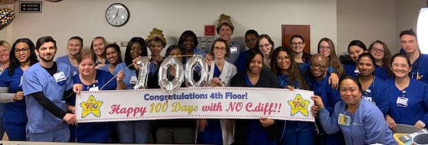 Duke Raleigh Hospital staff showing a sign that says celebrate 100 days with no instances of the hospital-acquired infection Clostridium difficile, also known as C.diff.