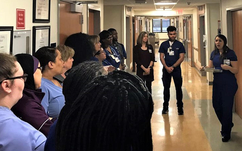 Hospital staff in a tiered huddle to discuss target-zero goals.