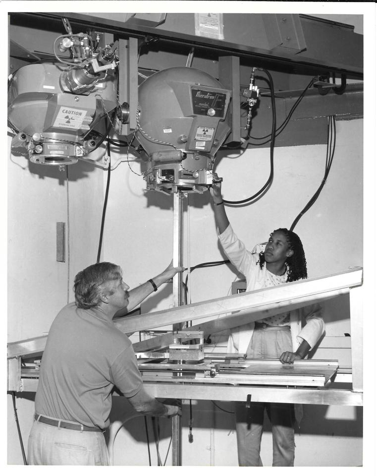 Two scientists on either side of a large machine with overhead components