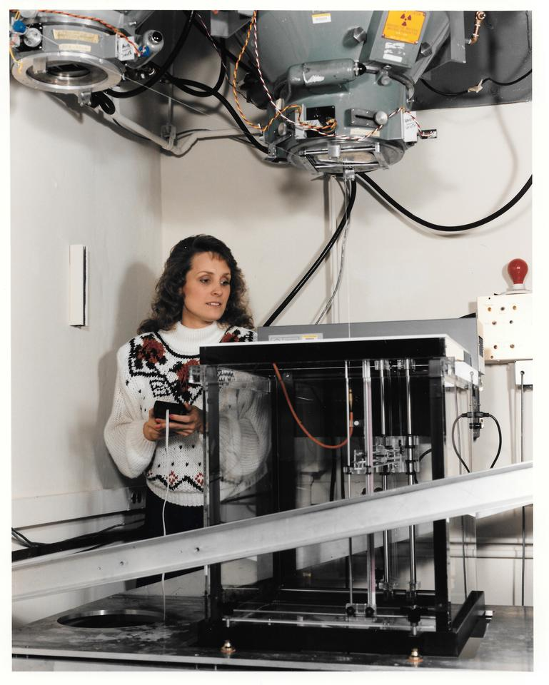 A woman adjusts a scientific device like a large box with overhead components