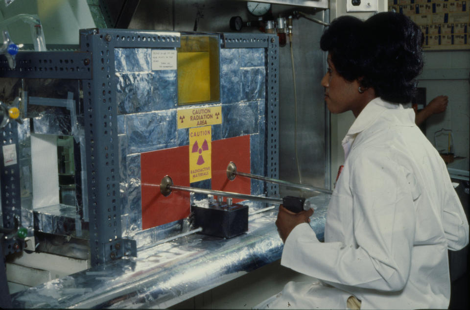 A woman works at a metal machine with a radioactivity warning sticker
