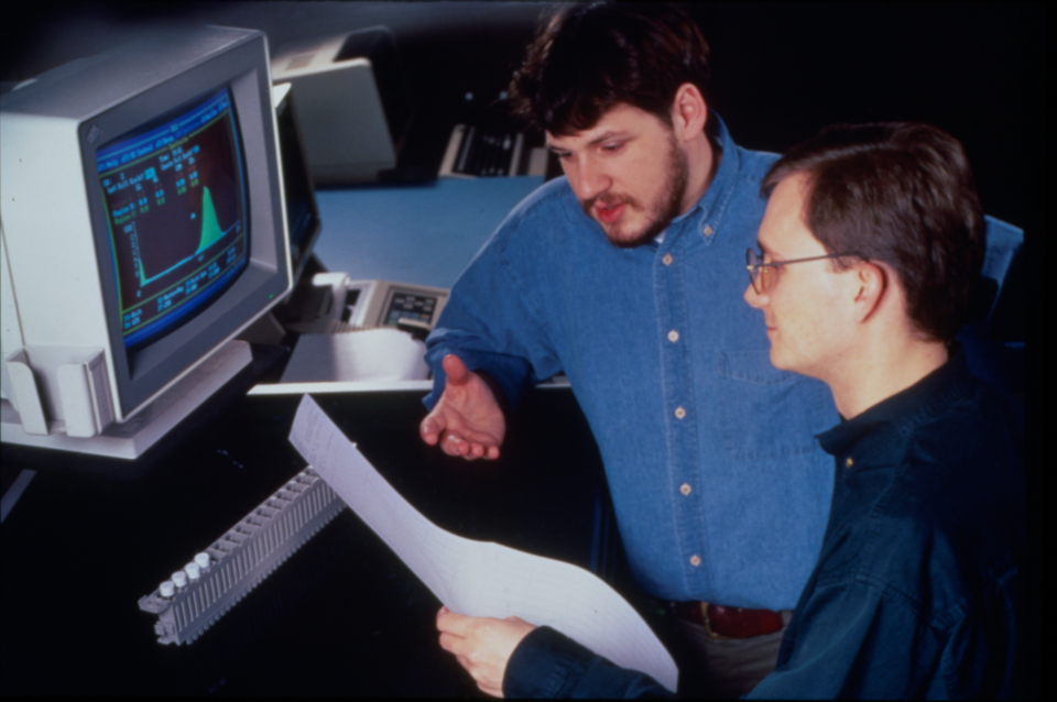 Two men look at a printout in front of a computer screen