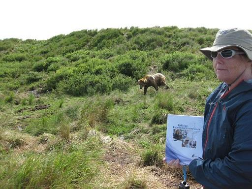 Maureen Washburn holds Baldrige booklet outdoors with a bear in the background