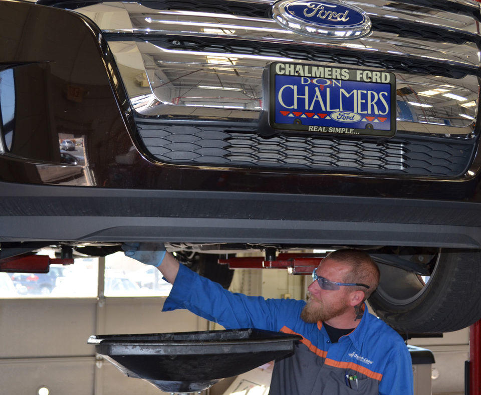 worker at Don Chalmers Ford is shown servicing vehicle