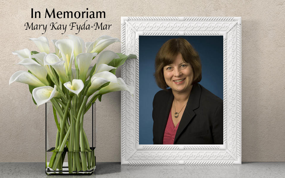 In Memoriam: Photo of Mary Kay Fyda-Mar with white lilies in a vase beside frame.