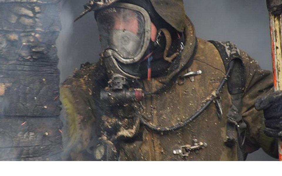 Firefighter wearing gear, including face shield, standing near smoking building